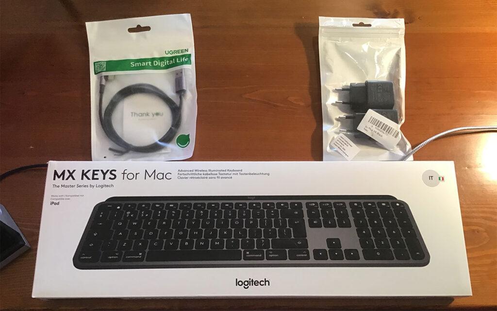 """Disabili DOC – """"Speciale Logitech MX Keys"""" – L'immagine mostra la tastiera """"MX KEYS for Mac"""", un cavo Ugreen USB A - USB-C con innesto angolato a 90º e degli alimentatori da 5V 2,4A"""