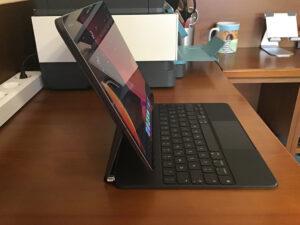 """Disabili DOC – L'immagine mostra l'iPad Pro 12,9"""" 2020 sulla Magic Keyboard, la vista laterale mette il evidenza il frutto del cavo magnetico inserito nella porta USB-C della tastiera"""