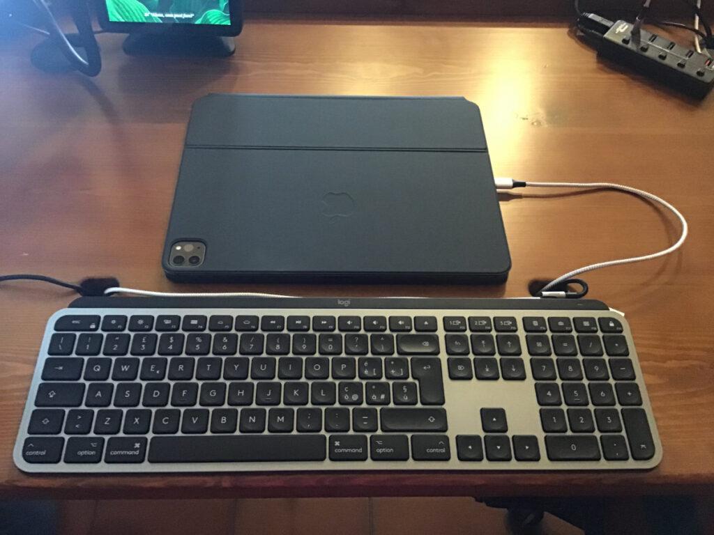 """Disabili DOC – L'immagine mostra l'iPad Pro 12,9"""" 2020 inserito nella Magic Keyboard chiusa, all'iPad è collegato un cavo magnetico per la ricarica"""